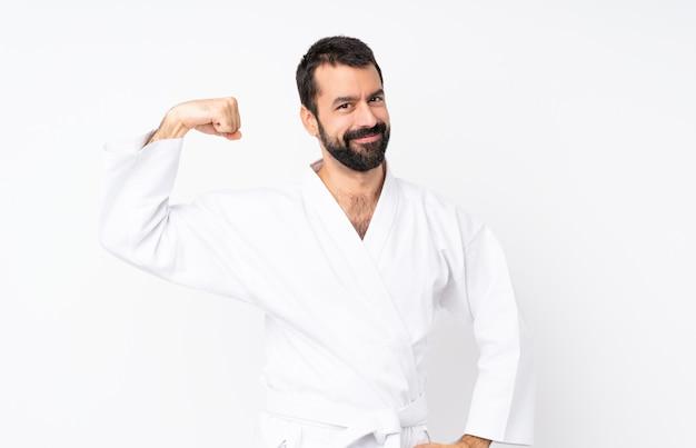 Jeune homme fait karaté sur un mur blanc isolé, faisant un geste fort
