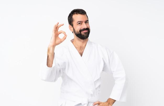 Jeune homme fait karaté sur mur blanc isolé, montrant un signe ok avec les doigts