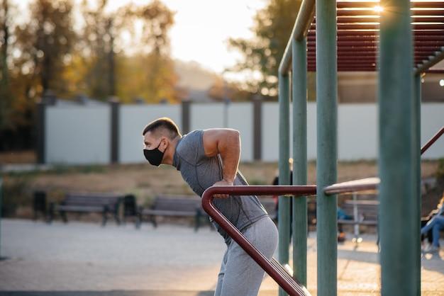 Un jeune homme fait des pompes sur un terrain de sport dans un masque lors d'une pandémie au coucher du soleil