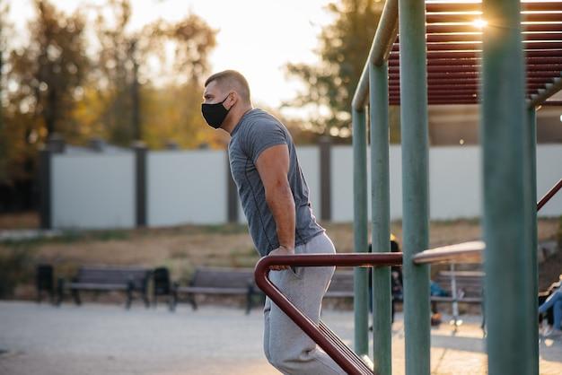 Un jeune homme fait des push-ups, des pull-ups sur un terrain de sport dans un masque lors d'une pandémie au coucher du soleil. sport, mode de vie sain.