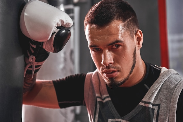 Jeune homme fatigué en vêtements de sport s'entraînant dur sur un sac de frappe lourd. sportif musclé avec des gants de boxe blancs regardant loin en se tenant debout dans une salle de boxe