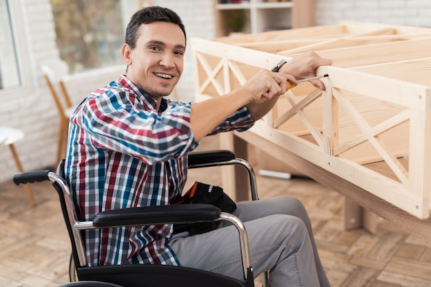 Un jeune homme en fauteuil roulant essaie de plier sa bibliothèque.