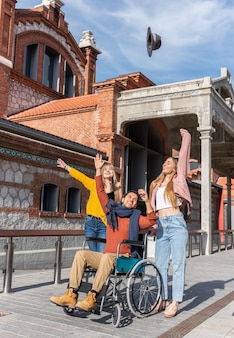 Jeune homme en fauteuil roulant jetant un chapeau avec deux jeunes femmes