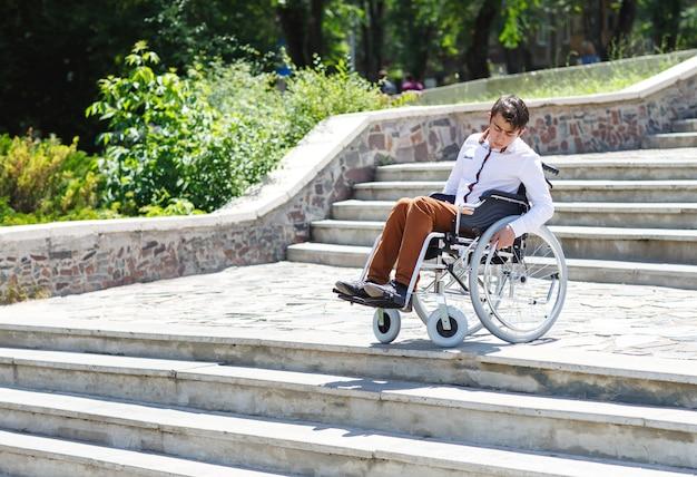 Un jeune homme en fauteuil roulant qui ne peut pas descendre les escaliers.