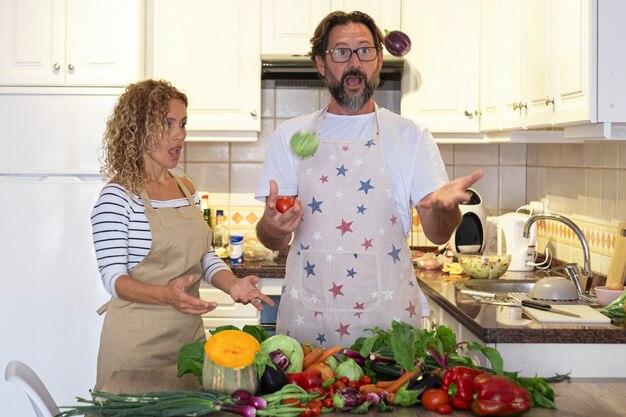 Un jeune homme et une femme adultes mûrs jouent et s'amusent dans la cuisine pendant la préparation du déjeuner avec des légumes frais. un couple heureux de personnes passe du temps ensemble à la maison