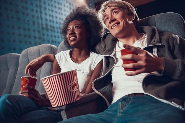 Jeune homme avec une femme afro-américaine au cinéma.