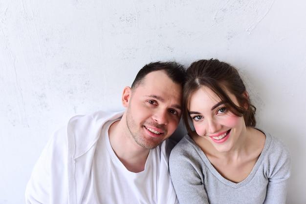 Jeune homme et femme assis côte à côte dans une pièce blanche