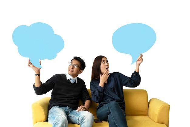 Jeune homme et femme assise sur le canapé tenant une bulle de dialogue sur fond blanc.