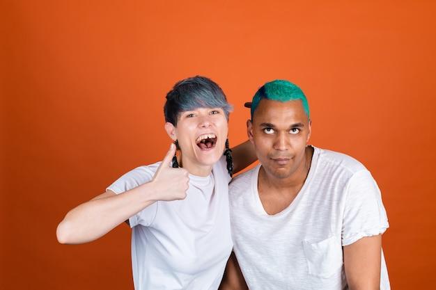 Jeune homme et femme en blanc décontracté sur un mur orange, femme avec des émotions folles, montre le pouce vers le haut