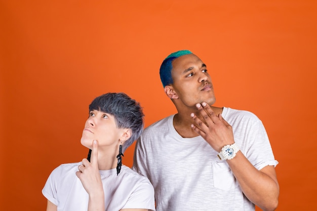 Jeune homme et femme en blanc décontracté sur un mur orange regard pensif de côté tenant le menton