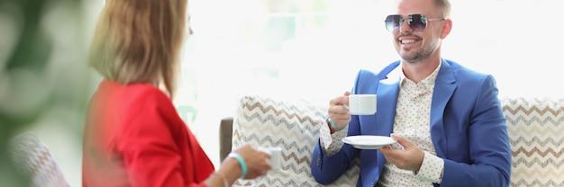 Jeune homme et femme buvant du café et communiquant au café