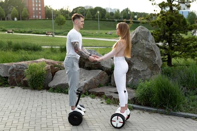 Jeune homme et femme à cheval sur l'hoverboard dans le parc