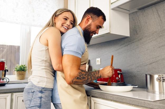Jeune homme et femme cuisiner des aliments dans la cuisine ensemble heureux couple préparer des aliments