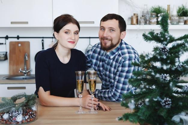 Jeune homme et femme dans la cuisine avec arbre de noël