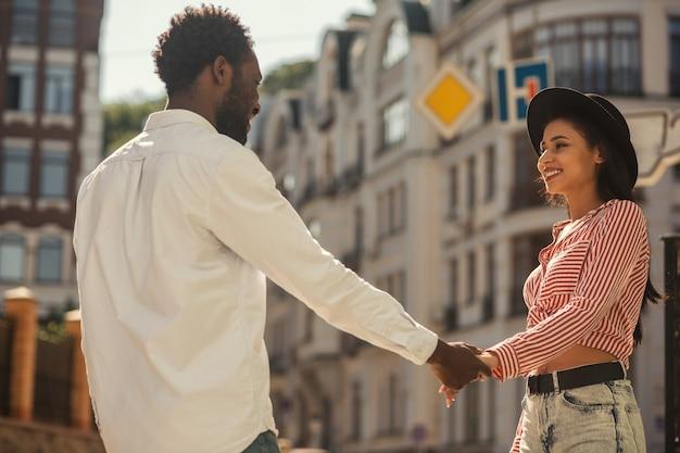 Jeune homme et femme debout face à face et se tenant la main tout en se souriant dans la rue