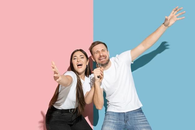 Jeune homme et femme émotionnelle sur un mur rose et bleu