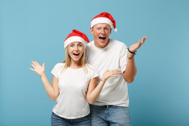 Jeune homme et femme excités d'amis de couple de santa dans la pose de chapeau de noël