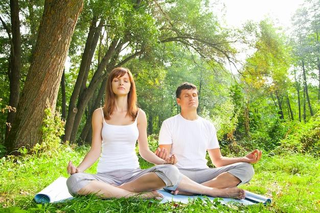 Jeune homme et femme faisant du yoga dans le jardin