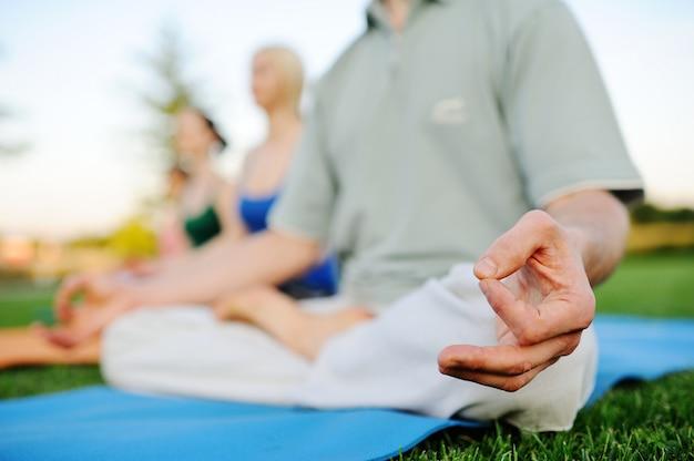 Jeune homme et femme faisant du yoga sur l'herbe fraîche