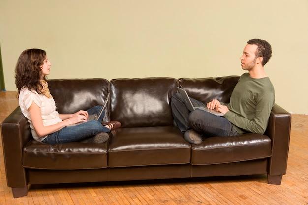 Jeune homme et femme informatique sur canapé