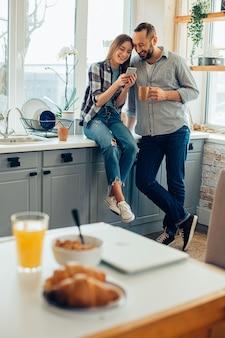 Jeune homme et femme joyeux souriant dans la cuisine et regardant l'écran d'un smartphone