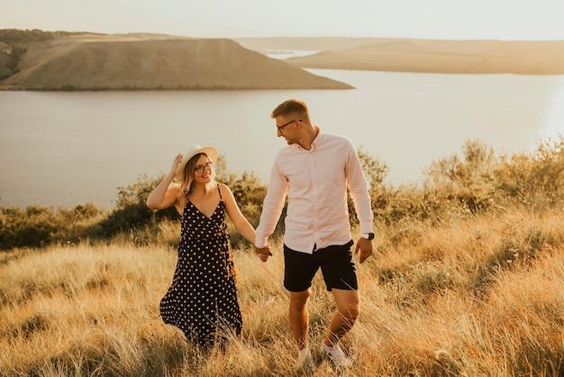 Jeune homme et femme marchant dans la prairie au coucher du soleil en été près du lac.