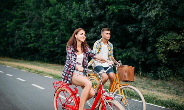 Jeune homme et femme marchant sur des vélos rétro