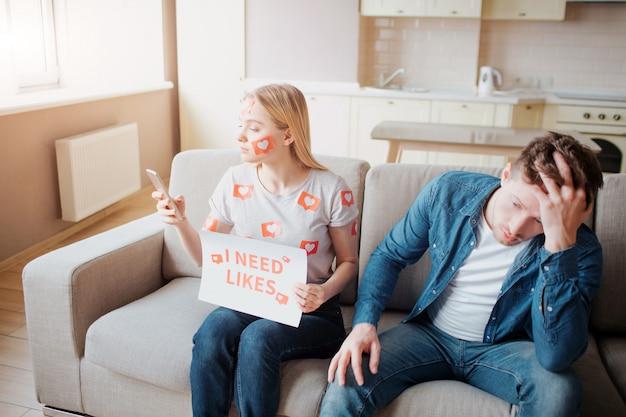 Un jeune homme et une femme ont une dépendance aux médias sociaux. dépendance des smartphones. femme regarde le téléphone. l'homme est fatigué.
