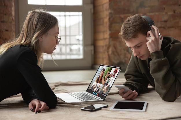 Un jeune homme et une femme participent à une vidéoconférence en regardant l'écran d'un ordinateur portable lors d'une réunion virtuelle, une application webcam d'appel vidéo pour les entreprises, en gros plan. travail à distance, freelance, éducation, concept de style de vie.