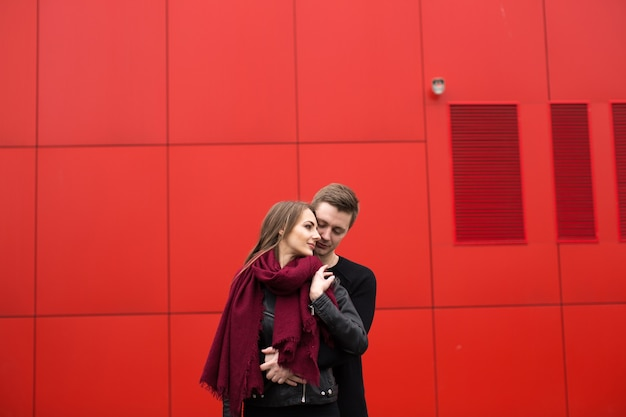Jeune homme et femme en passion, émotion, dans la rue avec en toile de fond le mur rouge. mode