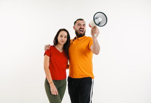 Jeune homme et femme portés dans les couleurs du drapeau lgbt sur fond blanc. modèles caucasiens en chemises lumineuses.