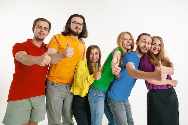 Jeune homme et femme portés dans les couleurs du drapeau lgbt sur un mur blanc. modèles caucasiens en chemises lumineuses. ayez l'air heureux ensemble, souriant et étreignant. fierté lgbt, droits de l'homme et concept de choix.