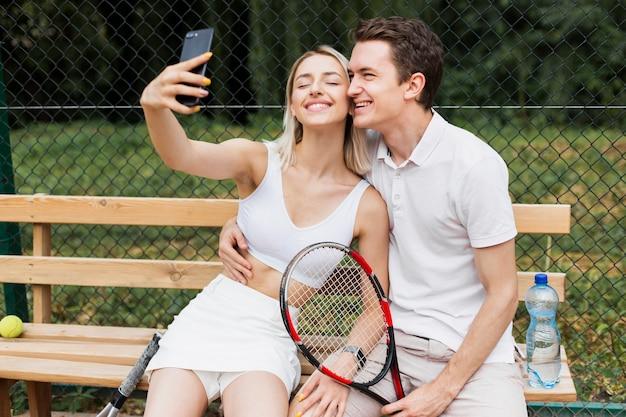 Jeune homme et femme prenant un selfie