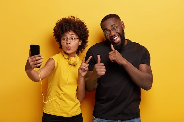 Jeune homme et femme prenant selfie