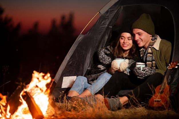 Jeune homme et femme profitant d'un feu de joie