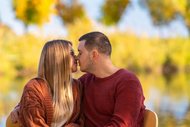 Jeune homme et femme profondément amoureux assis bras dessus bras dessous se préparant à s'embrasser