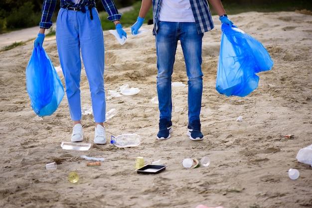 Jeune homme et femme ramassant des ordures en plein air.