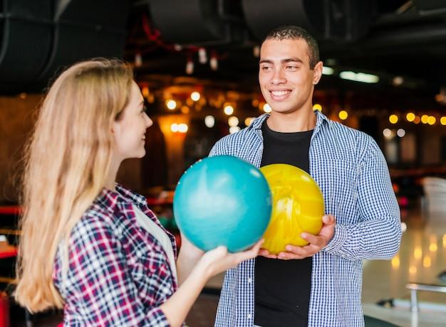 Jeune homme et femme s'amusant dans un club de bowling