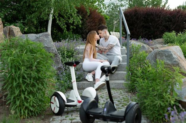 Jeune homme et une femme s'embrassent dans le parc au premier plan hoverboard