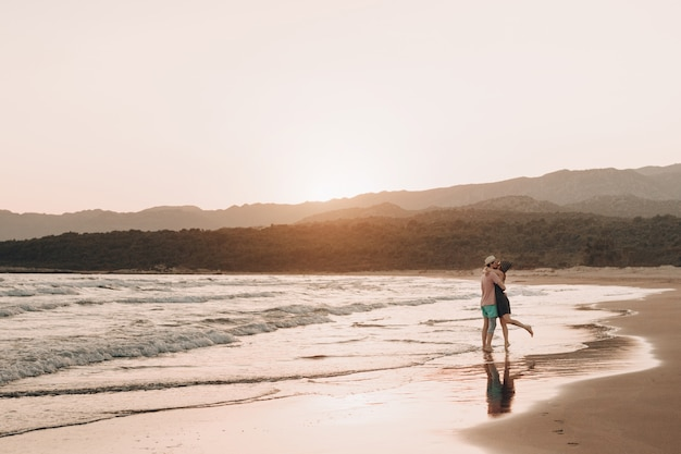 Jeune homme et femme s'embrasser sur la plage au coucher du soleil.