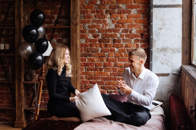 Un jeune homme et une femme se battent avec des oreillers sur un lit dans une chambre de style loft