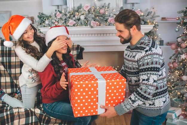 Jeune homme et femme tenant une grande boîte de cadeau. l'enfant ferme les yeux de sa mère. l'homme regarde sa femme. la famille porte des vêtements de fête.