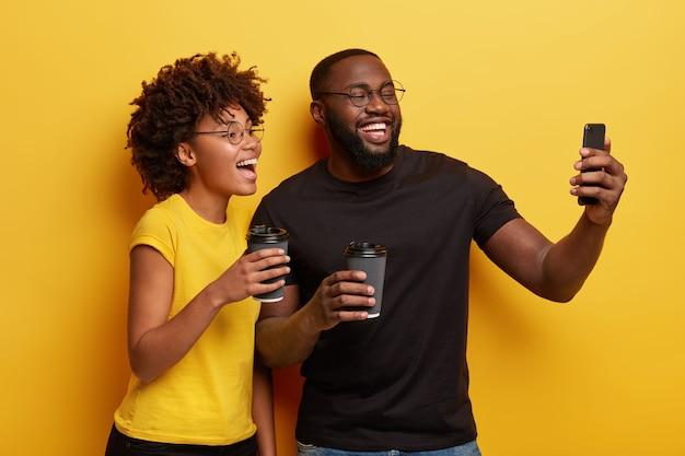 Jeune homme et femme tenant des tasses de café