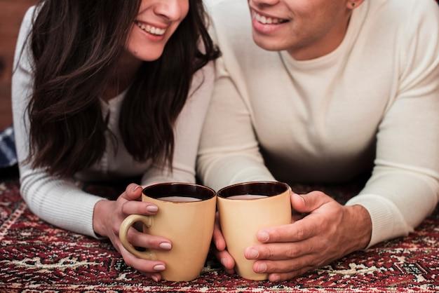Jeune homme et femme tenant des tasses
