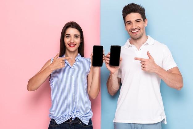 Jeune homme et femme en tenue décontractée tenant les téléphones mobiles ensemble, isolé sur un mur coloré