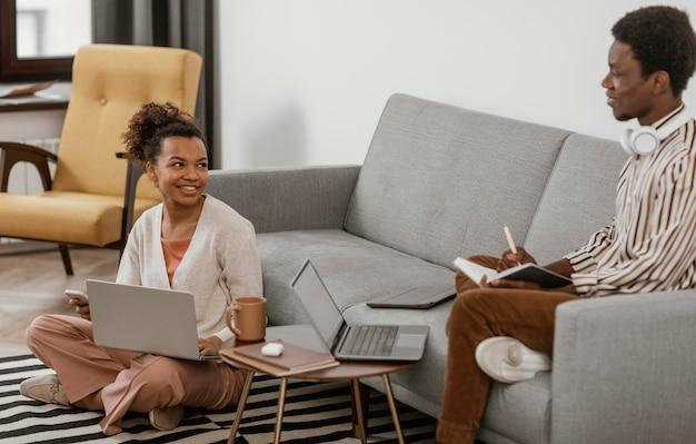 Jeune homme et femme travaillant à domicile