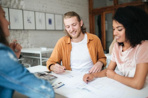 Jeune homme et femme travaillant ensemble au bureau