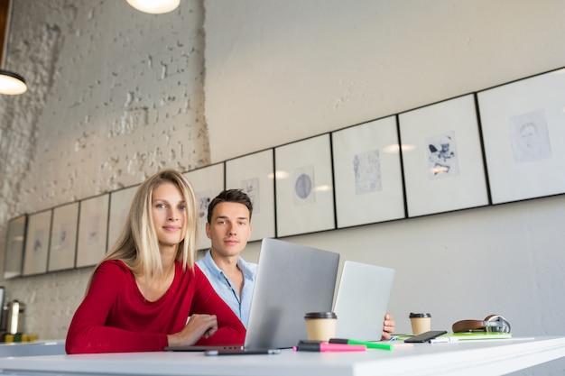 Jeune homme et femme travaillant sur un ordinateur portable dans un espace ouvert, bureau de travail collaboratif
