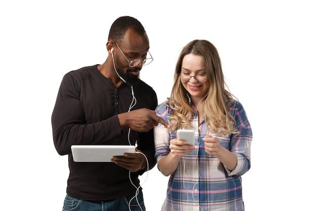 Jeune homme et femme utilisant un ordinateur portable, des appareils, des gadgets isolés sur fond de studio blanc.