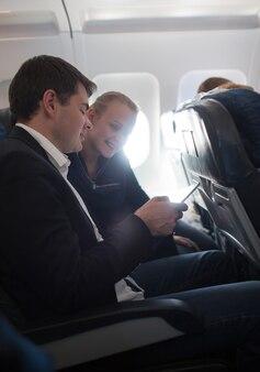 Jeune homme et femme utilisant un téléphone portable en avion